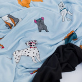 Two sided view of our Must Love Dogs adult swaddle blanket.  Dogs featured on blue with a black backing.