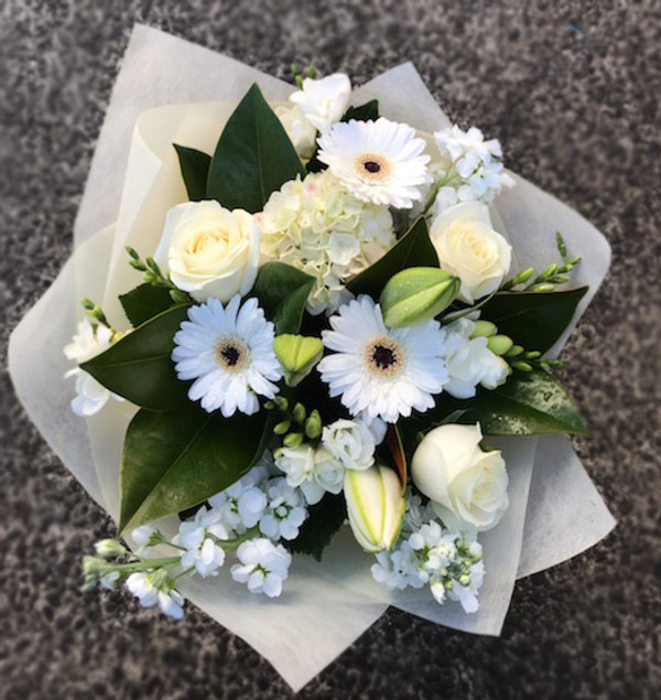 A bouquet of flowers in classic white, hand tied and presented in our signature wrap