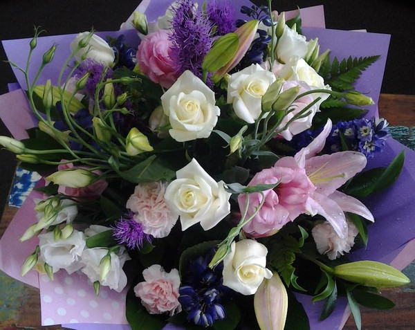 A beautiful mix of flowers that remind you of a cottage garden.  The arrangement is a handtied bouquet in our signature wrap with a soft chiffon ribbon bow.  Some flowers will vary depending on season eg Lisianthus are available during summer only.
