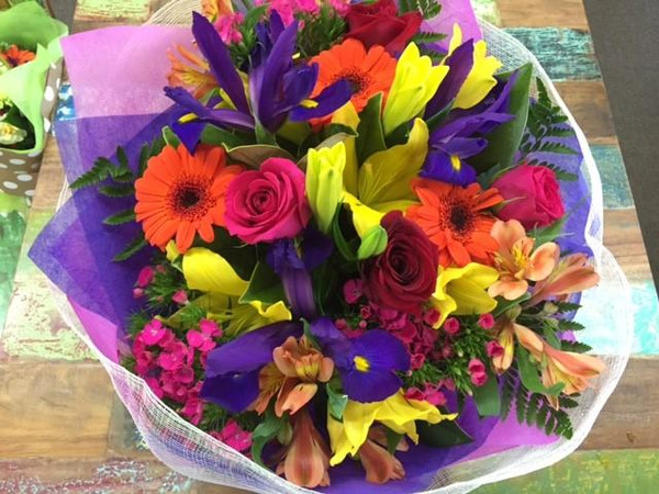 A statement arrangement of colourful flowers in a handy cardboard vase called a vox. These flowers can be delivered and readily enjoyed. A beautfiul cinimay wrap to compliment the colour arrangement, tied with a chiffon ribbon. Butterfly not included unless requested.