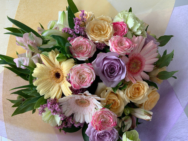 A Pretty & Sweet arrangement of flowers in a handy cardboard vase called a Vox.  These flowers can be delivered and readily enjoyed.  A beautiful  wrap to compliment the color arrangement, tied with a chiffon ribbon.