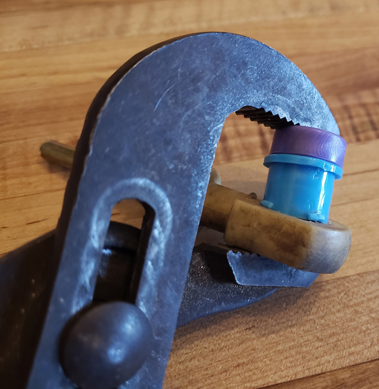 Step 3:  Place driver under thumb and bushing 'tang' or teeth edge down away from driver as shown. May use thumb or pliers as shown to push or press  bushing into place.
