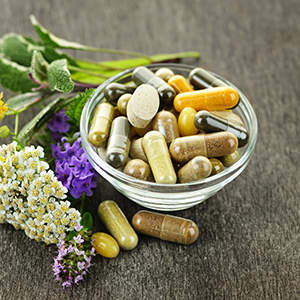 Picture of a bowl of supplement capsules with some flowers and  herbs next to it.