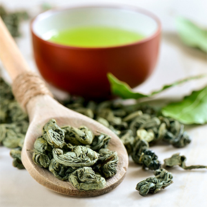 Picture of a cup of green tea with dried tleaves on a wooden spoon.