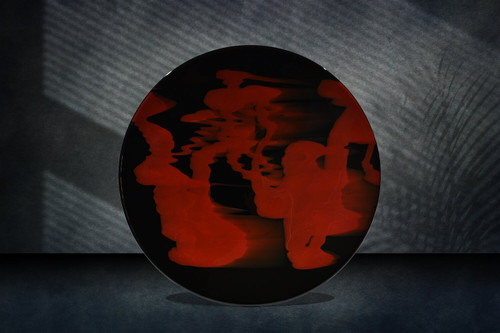 "18.5""d One of a kind red calligraphy-like image on black art glass. Shallow drop. Shown standing."