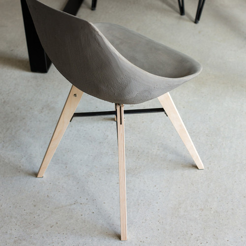 concrete chair incorporates wooden feet for a warmer rendering