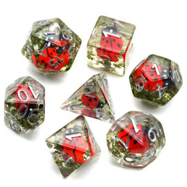 This clear resin dice set contains small (wooden?) red ladybugs nestled in green moss.