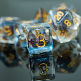 These clear resin dice each contain a miniature sailboat.