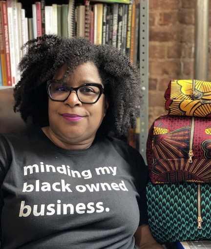 photo of black woman with an afro wearing a t-shirt that reads: Minding my own Black Business. Woman is seated next to three large and colorful zipper pouches.