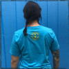 This is the back view of the Strong Athletic Mom Crew Neck T-shirt in Aqua Blue with Yellow Ink. The Strong Athletic logo stands out in it's yellow ink, on the back of this shirt. This shirt is comfy and it's preshrunk so you don't have to worry about shrinking it the first time you put it in the wash. Strong Athletic is a company that is owned and run by queer women who are also feminist. We believe that all people should be included within sports, and that includes moms, mothers and mommies.