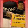 """Every time we send out a Strong Athletic product we make sure to wrap it in a wrap that reads, """"You are so Strong"""", and we seal the wrap with one of our signature Strong Athletic stickers. We also include a postcard that tells you our origin story on one side, and that has our Strong Athletic ____________ art on the other side. We always hope that you'll write in what ever third word is the most meaningful to you on that post card. We always send a few stickers, including any that you choose to add to your order. All of our stickers, including the ones that we send with your shirt, are produced in the US by small-scale sticker company. We're a company that doesn't believe in mass buying or mass production. This means that when we order something online, we want the experience to be special and unique. We assume the same is true for people buying products from our site. It's for this reason we put so much care into packaging and sending your Strong Athletic item. If this is a gift, you can even include instructions for a hand written note that we will include with the package. We hope you enjoy! And if you do, we hope you consider writing us a review about your product."""