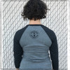 This is the back of the Strong Athletic Queer two-toned gray Baseball T-shirt white white ink designed by Strong Athletic.  The Strong Athletic logo is printed in black ink in the space between the shoulder blades. The sleeves are three-quarter length and in a dark-grey color, the body of the shirt is a heather-grey.