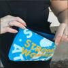 This is the Strong Athletic Woman Light Blue Fanny Pack with Yellow Ink made for Strong Athletic by Flat Track Revolution. The bags are made out of a heavy weight coated canvas fabric that is water resistant. The bags come with an adjustable nylon strap that has a side release plastic buckle. These bags are easy to open and close because of the zippers that we use.