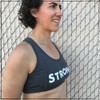 Looking for the perfect sports bra to wear to the gym on lifting or cardio days? This is a side view of the Strong Sports Bra by Strong Athletic. The word Strong is printed in bold, distressed white letters across the chest. The design of the bra has two seems running on the outside of the bust, making it so the shape of the chest when wearing the bra is very complimentary.