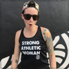 This is the front view of the Strong Athletic Woman Black Performance Racerback Wicking Tank Black with White Ink by Strong Athletic. The words on this black tank are printed in white ink. The Strong Athletic logo is printed on both the front and the back of the tank. This shirt is made by Strong Athletic the company that supports women, girls and the LGBTQIA2S+ community in sports and athletic. Strong Athletic made the Strong Athletic Woman design because we want to amplify the voices of all the strong women in the world, working to make a difference for girls and women in sports.