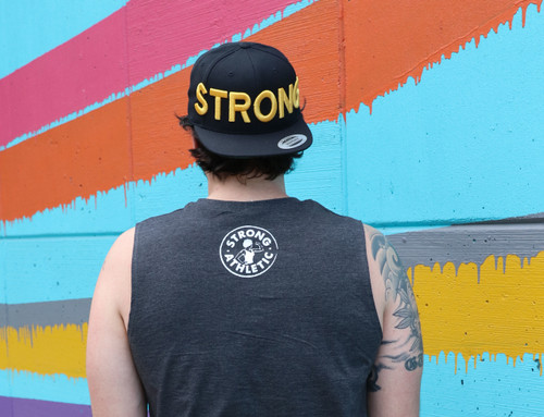 "Strong Hat by Strong Athletic. Gold Letters on a Black Snapback by Yuppong. Embroidered in Austin, Texas. If you've ever wondered, ""who makes the strong hat?"" now you know."