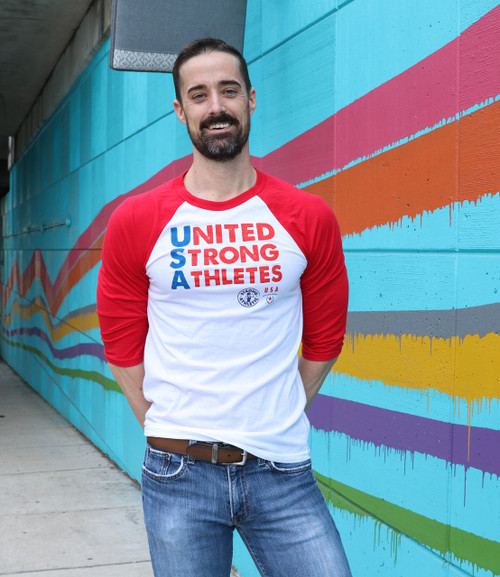 Front of the United Strong Athletes baseball t-shirt. This is a gender neutral Bella and Canvas shirt. The sleeves end right below the elbow. The shirt is white and the ink is red and blue. 50 % of the profits gets donated to USA Roller Derby Use the tag #unitedstrongathletes when tagging us.