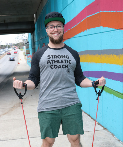 """This is the Strong Athletic Coach Baseball T-Shirt by Strong Athletic. Behind every badass athlete is a coach who supports them. Get this shirt for your favorite coach if you need a """"thank you"""" gift at the end of the season to tell them they're awesome! This is Chad, one of our favorite coaches. He inspires us to push ourselves, I bet yours does too."""