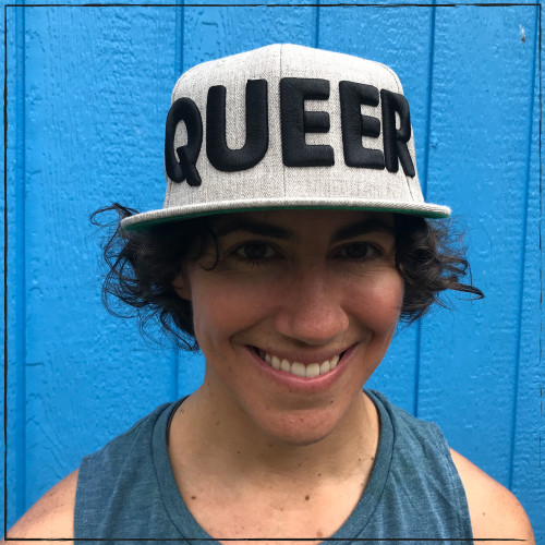 """This is the front of our Queer hat. This heather grey snapback has the word """"queer"""" embroidered in thick 3-D letters on the front of the cap. The Strong Athletic logo is stitched on to the back of the hat in black thread."""