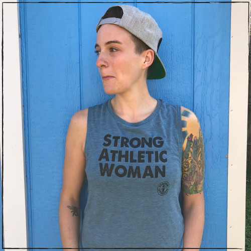 This is the Strong Athletic Woman Muscle Tank on an actual strong, athletic woman. We love the deep heather teal color with the contrasting black ink letters. The shirt is bold, and perfect for the bold women who wear it.  We print this design on the Bella Canvas Flowy Muscle Tank 8803. #strongwoman #strongathletic #strongathleticwoman
