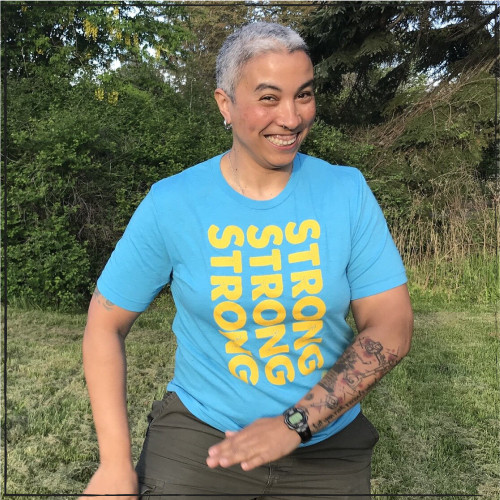 """From the creators of the """"Strong Athletic Woman"""" line is the  Strong, Strong, Strong Vertical Crew Neck T-Shirt in Heather-Aqua-Blue with Yellow Ink. Just as Sorrell is dancing in the photo, these bright color will make you wanna dance, and smile, and be active."""