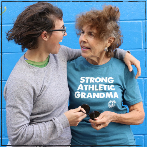 This is the front of the Strong Athletic Grandma All-Gender T-shirt in Heather Teal with White Ink. It is worn by Nona Kean, the mother of Nadia Kean who owns Strong Athletic. This photo was taken at the Strong Athletic photo shoot by Michele Hale when neither Nadia nor Nona knew they were having their photo snapped. The intimacy between a mother and her daughter comes through in the photo.  #Strongathleticgrandma , #strongathleticgrandmother , #strongathleticmom , #grandma #stronggrandma, #stronglikegrandma , #strongathleticwoman , #ilovemygrandma , #strongathletic , #womanownedocompany , #womeninsports