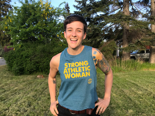 This is the front of the Strong Athletic Woman Deep Heather Teal with Yellow Ink Crop Racerback Tank Top by Strong Athletic. Printed on the super soft and lightweight Bella Canvas Crop, this tank is perfect for working out in or simply making a statement.