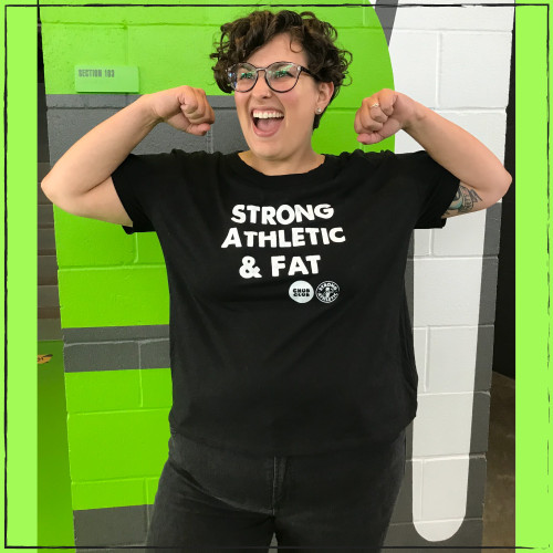 This is the front of the Strong Athletic & Fat T-shirt made by Strong Athletic in collaboration with Chub Club. Strong Athletic knows that an athlete's body size has nothing to do with their athleticism or strength. We know that there are too many humans in the world having to educate the population about the damaging impact of body shaming and we stand with body positive humans in their quest to do that work. Read more about why Wendy, the brains behind this t-shirt idea, requested this Design in her blog post.