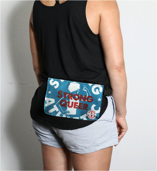 """This is the Strong Queer Fanny Pack by Strong Athletic, made for us by Flat Track Revolution. The fabric is a durable, waterproof light blue material. The Strong Athletic logo is printed in white ink and the words """"Strong Queer"""" are printed in red ink over the artwork. The strap comes in two different lengths and is adjustable, so you can wear it around your back (as seen in the photo) or your waste, or you can take the strap off and use it like a clutch."""