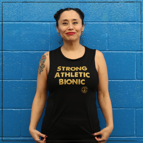 This is the front of the Strong Athletic Bionic Muscle Tank, printed on a solid black Bella Canvas Flowy Muscle Tank, 8803. The words are printed in gold ink on the front. The arm holes of this tank are cut to be low enough to see a bit of your bra, but not so much. This tank is probably the most popular style of tank that Strong Athletic has. #strongathletic , #strongathleticbionic , #rollerderbylife ,  #bloodsweatandtears , #bionic , #bionicwoman , #bionicman , #rollerderby , #strongathleticskater