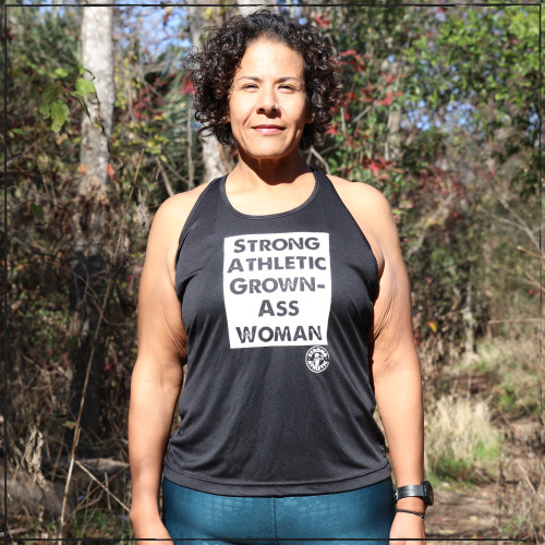 This is the front of the Strong Athletic Grown-Ass Woman Racerback Performance Racerback Wicking Tank. We created this black workout tank top because the words on the front are simple, straightforward and true. We want women to continue to tell the world that they are over being marginalized in every facet of everyday life, sports included.