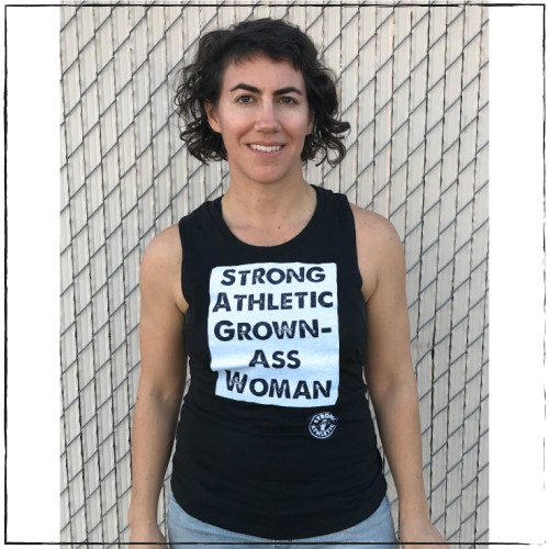 This is the Strong Athletic Grown-Ass Woman Muscle Tank printed on the District Tank Top. This tank is designed to be tighter fitting. It comes down to upper thigh, so if you wanna wear this design, but you don't want a crop top, this is the option for you. This drop arm muscle tank is super comfortable and soft, making it so that it moves easy with your body regardless of if you're wearing it at the store or at the gym.