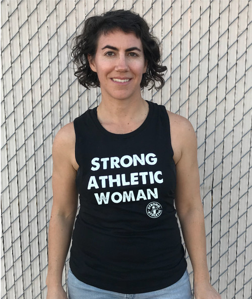 This is the front of the Strong Athletic Woman Black Muscle Tank with white ink. Printed on the District Concert Muscle Tank, this design is laid back and comfortable. We choose this style of shirt because we like how it's not flowy, and the material is so soft, yet durable. This is our original design. One that was created by Cristen Perks in 2013 for Strong Athletic owner Nadia Kean.