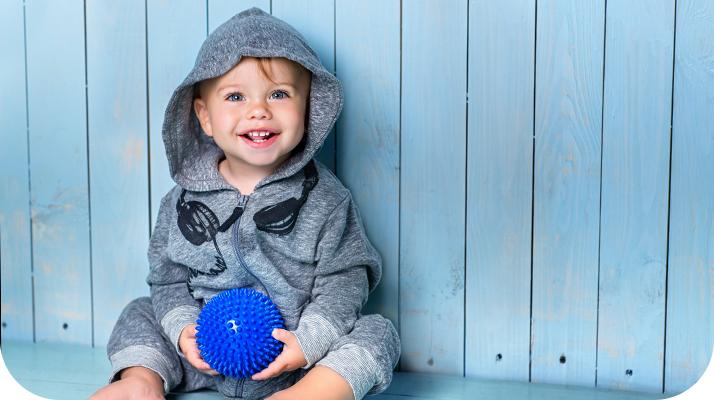 un niño pequeño con capucha y un jugete