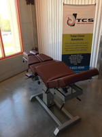 Omni Air Drop Elevation Chiropractic adjusting table viewed from back with leg section raised, color oxblood.