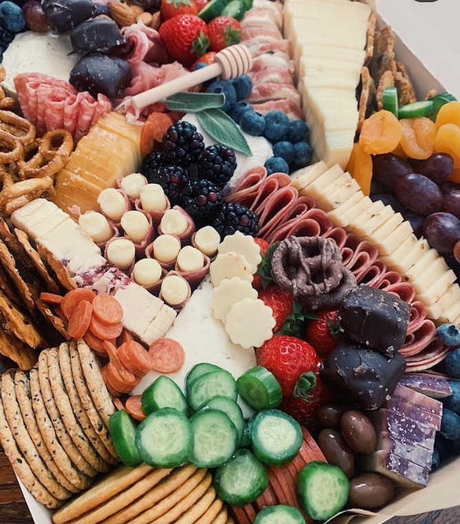 Artisan charcuterie and gourmet grazing boards are curated with a variety of cheese, charcuterie meats, fruits, nuts and yummy nibbles. Every box is seasonal, sourced regularly so they are subject to availability and substitutions. All boards come with wooden knives, a honey dipper, and everything you may need to be ready and enjoy!
