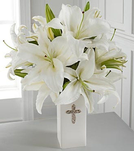 "This striking display of pure white lilies will send your heartfelt expressions when words just aren't enough. Arranged in a white ceramic vase and enhanced by a silvertone cross, this arrangement is perfect for First Communion celebrations, confirmations, sympathy, weddings or a special anniversary. Approximately 20""H x 15""W. Lilies may arrive in various stages of development. The lily blooms will continue to open, extending arrangement life - and your recipient's enjoyment."