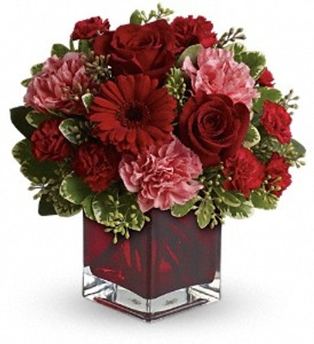 "Whether you'd like to send a message of love to that special someone, best friend or family member, this charming, crimson-hued bouquet will be a lovely sentiment of your affection.  A mix of roses, carnations and more in shades of red and pink accented with greenery.  Approximately 11"" W x 10"" H"
