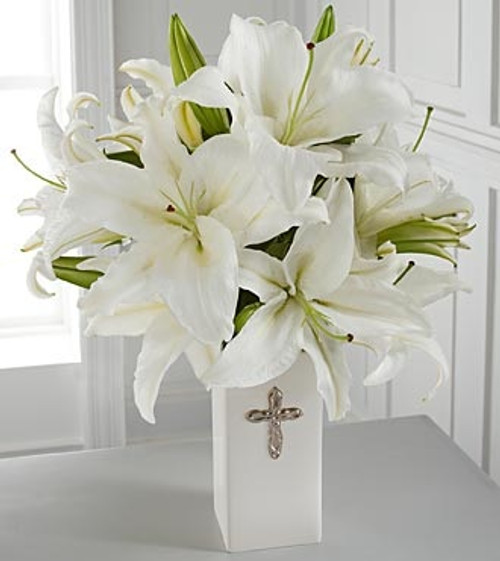 """This striking display of pure white lilies will send your heartfelt expressions when words just aren't enough. Arranged in a white ceramic vase and enhanced by a silvertone cross, this arrangement is perfect for First Communion celebrations, confirmations, sympathy, weddings or a special anniversary. Approximately 20""""H x 15""""W. Lilies may arrive in various stages of development. The lily blooms will continue to open, extending arrangement life - and your recipient's enjoyment."""