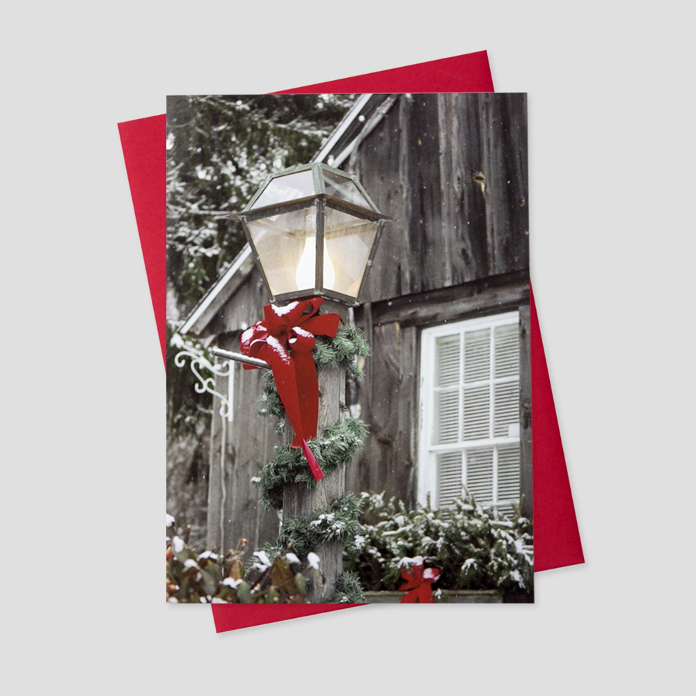 Professional Holiday greeting card featuring a lit lamp post decorated with a holiday bow lighting the night of a new snowfall