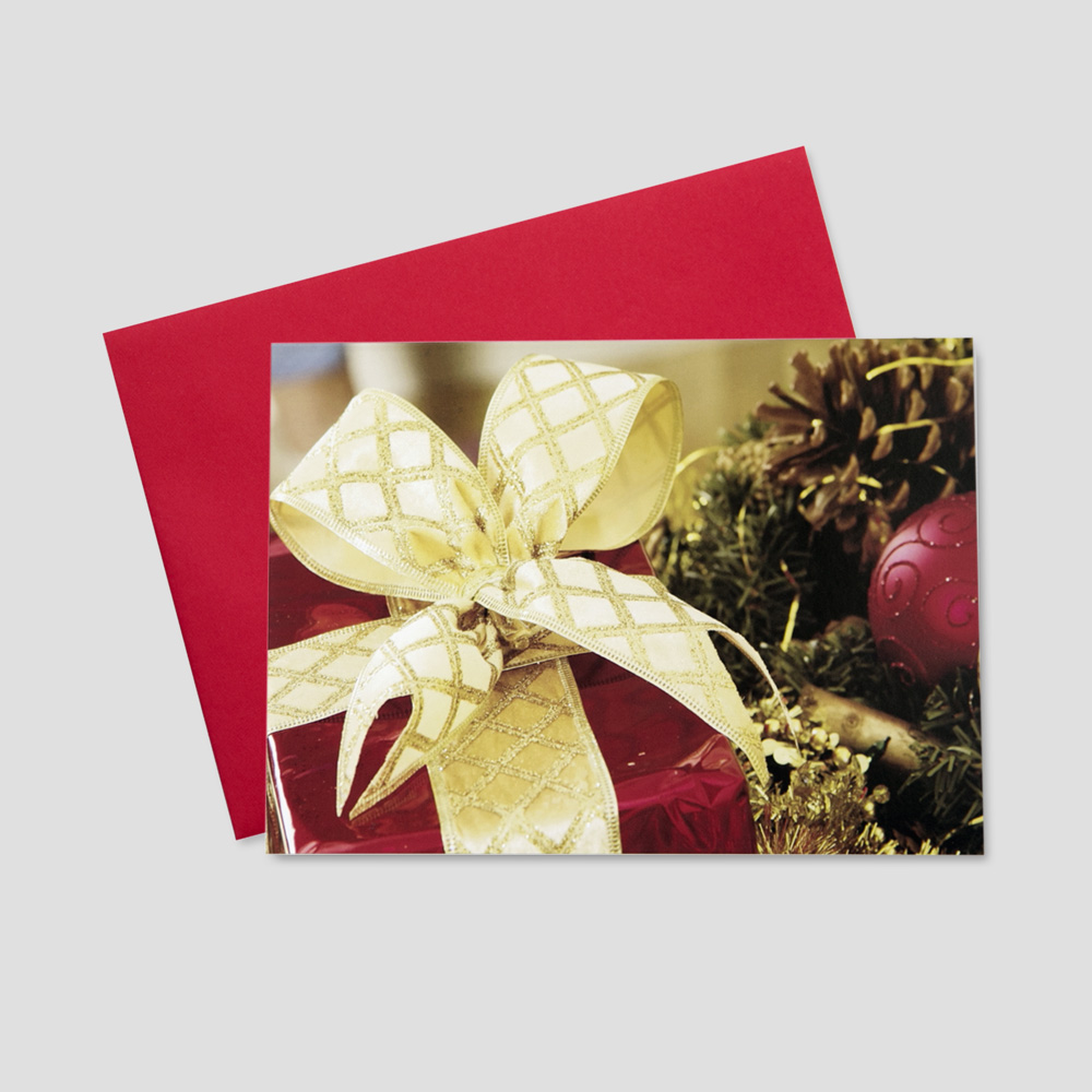 Corporate Christmas greeting card with a large present adorned in beautiful wrapping paper and a golden bow and surrounded by holiday elements