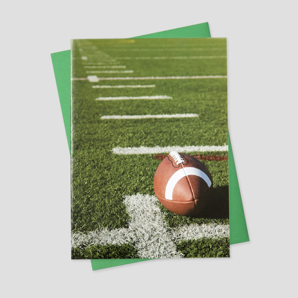 Business keep in touch greeting card featuring a neatly trimmed and lined football field and a new football placed on the field