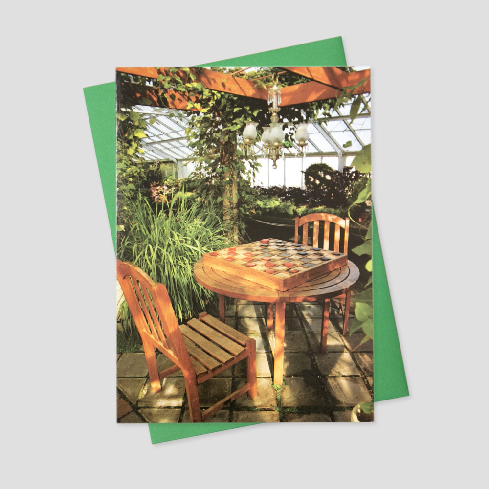 Company keep in touch greeting card featuring an outdoor scene in a greenhouse and a table set for two people playing a game of chess