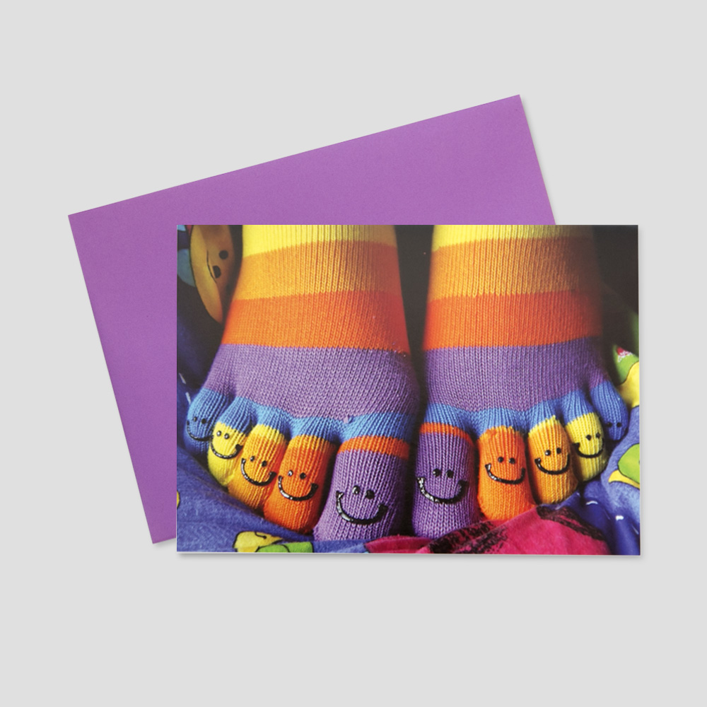 Humorous keep in touch greeting card with bright, colorful socks that have smiley faces on the toes