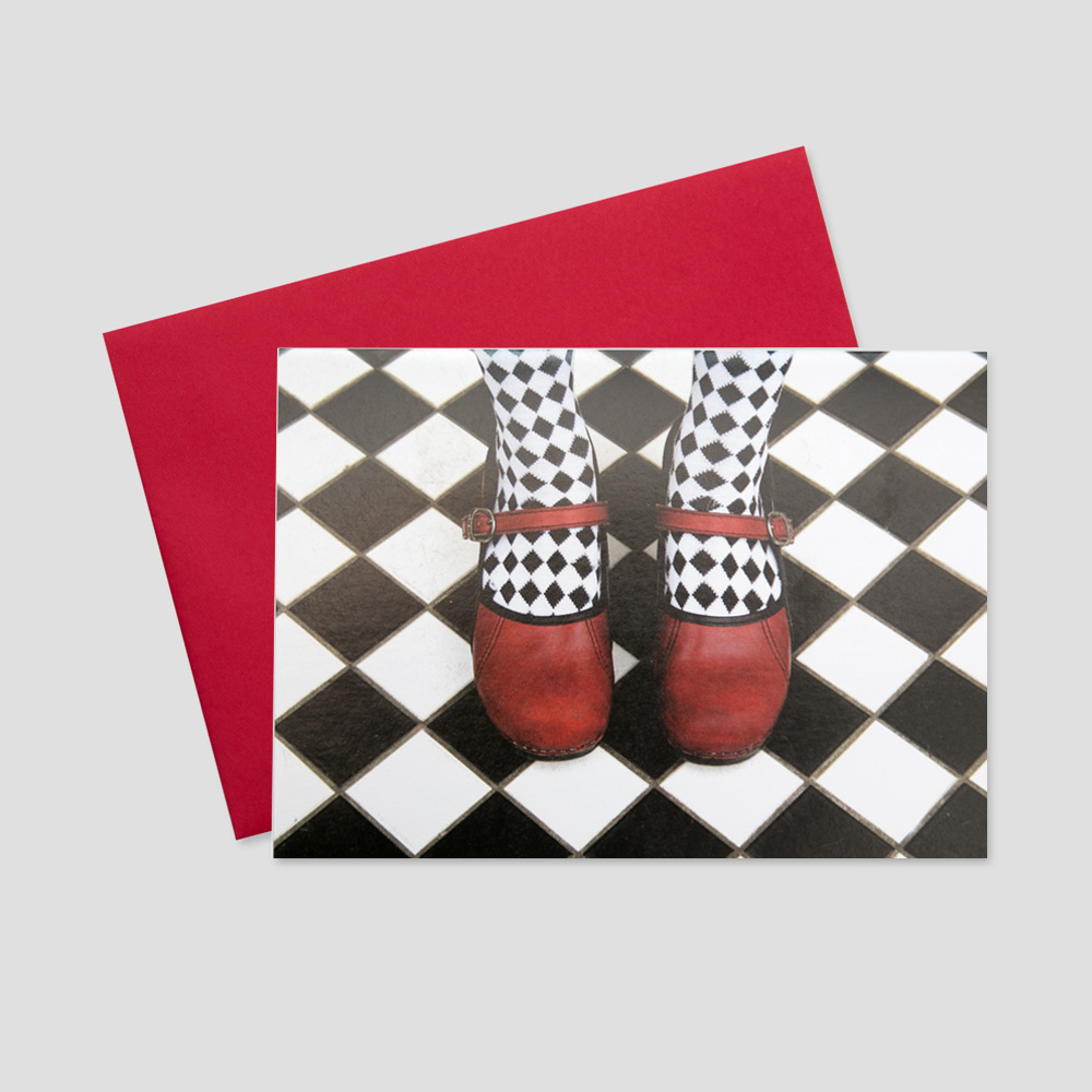 Keep in touch greeting card with a black and white checkered background and a pair of red ballet shoes as the focus