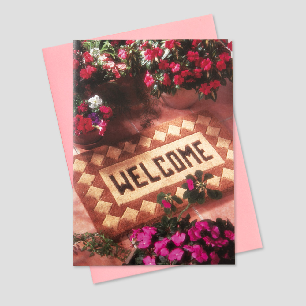 Realtor and Mortgage Broker greeting card featuring a brown welcome mat on the front porch of a home surrounded by colorful flowers