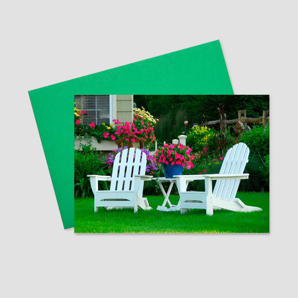 Customer Springtime greeting card with an image of a manicured lawn and two white chairs set neatly in the center