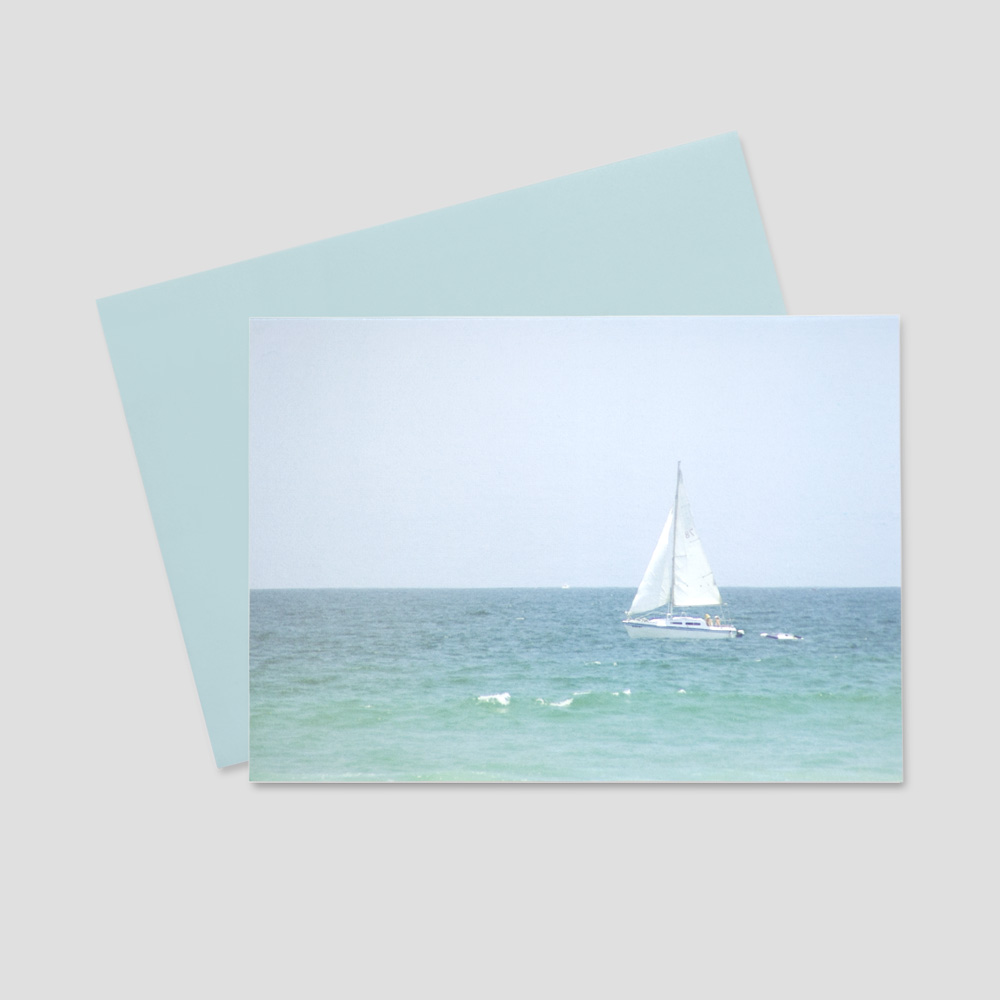 Professional Summertime greeting card with a sailboat sailing on a peaceful, beautiful blue sea