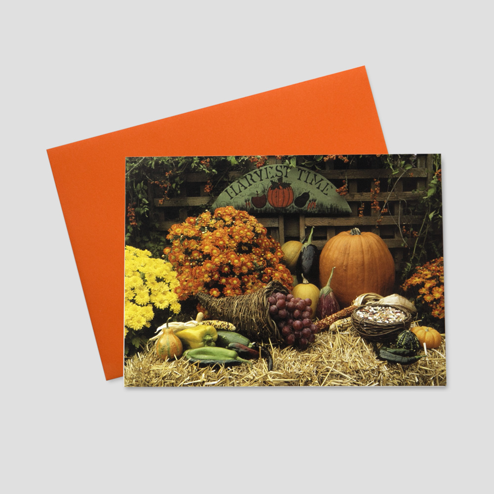 Thanksgiving greeting card featuring a scene of fall items on bales of hay and a harvest wagon