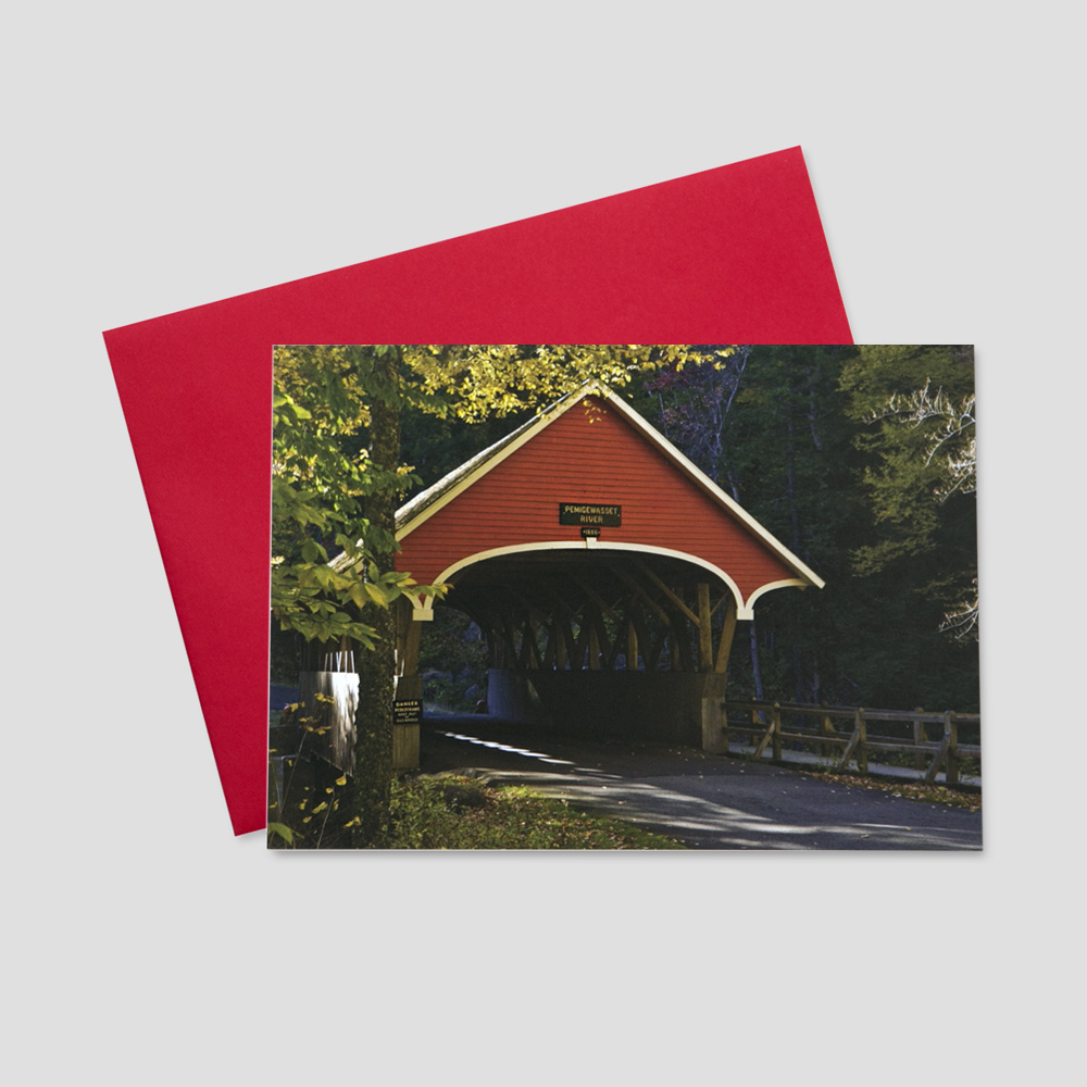 Professional Thanksgiving greeting card with an image of an old, red covered bridge amidst fall trees and leaves